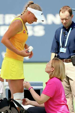 NEW HAVEN, CT - AUGUST 23:  Caroline Wozniacki of Denmark receives treatment from WTA trainer Kerri Whitehead during her match against Dominika Cibulkova of Slovakia during the New Haven Open at Yale at the Connecticut Tennis Center at Yale on August 23, 2012 in New Haven, Connecticut.  (Photo by Matthew Stockman/Getty Images) Photo: Matthew Stockman, Getty Images / 2012 Getty Images