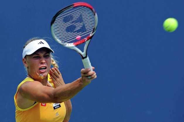 Caroline Wozniacki, of Denmark, hits a forehand return during her 6-2, 6-1 victory over Dominika Cibulkova, of Slovakia, in the quarterfinals of  the New Haven Open tennis tournament in New Haven, Conn., on Thursday, Aug. 23, 2012. (AP Photo/Fred Beckham) Photo: Fred Beckham, Associated Press / FR153656 AP