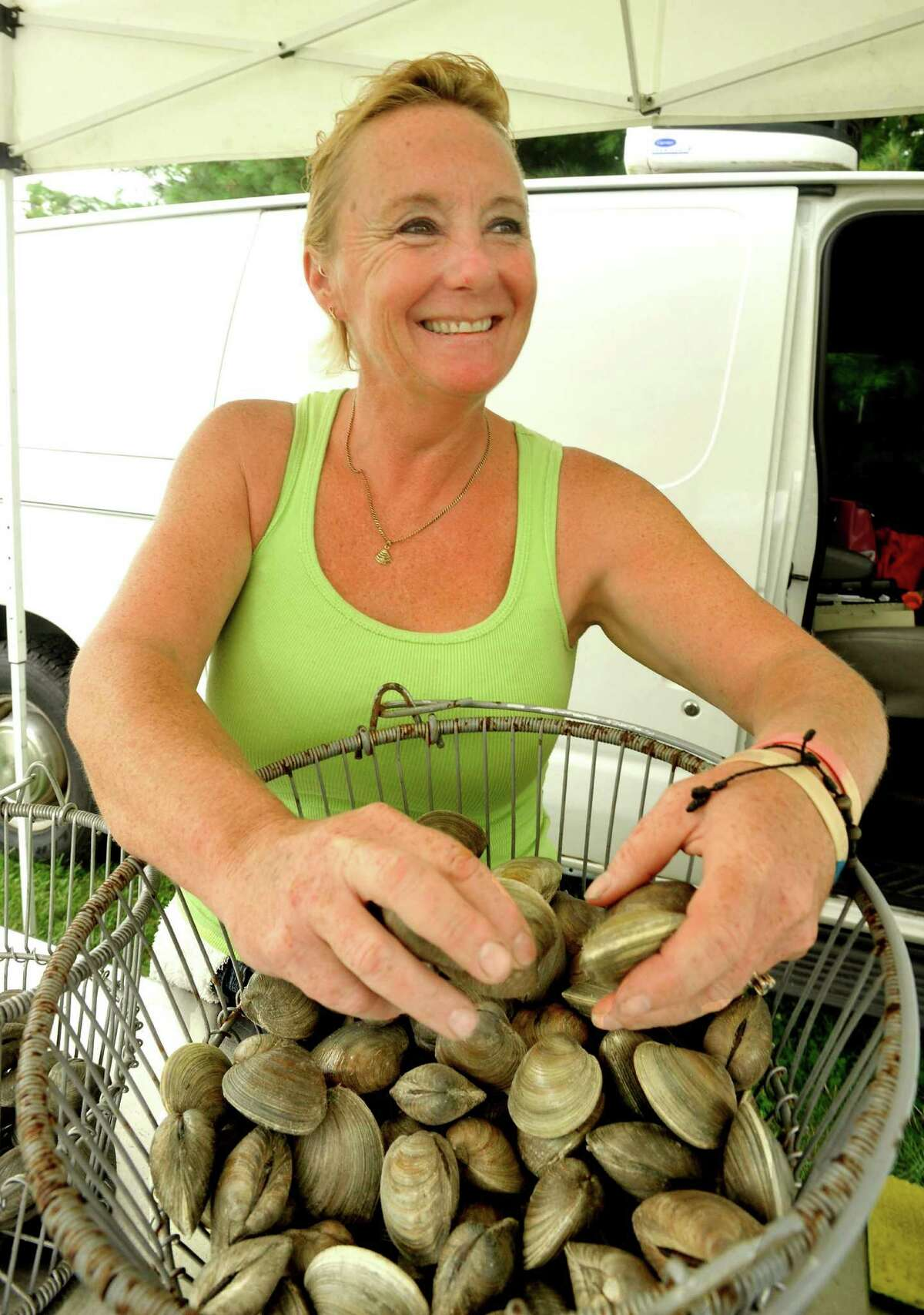 Laurie Popadic offers freshly caught clams at Pepe's Cream of the Crop Shellfish Farm stand during the City Center Danbury Farmers' Market on Friday, July 8, 2011