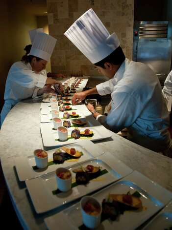 Chefs Michelle Hitchcock (left) and Fareez Dossari work on the salad display at Nao, which is being staffed by students at the San Antonio campus of the Culinary Institute of America. Photo: Robin Jerstad, For The Express-News