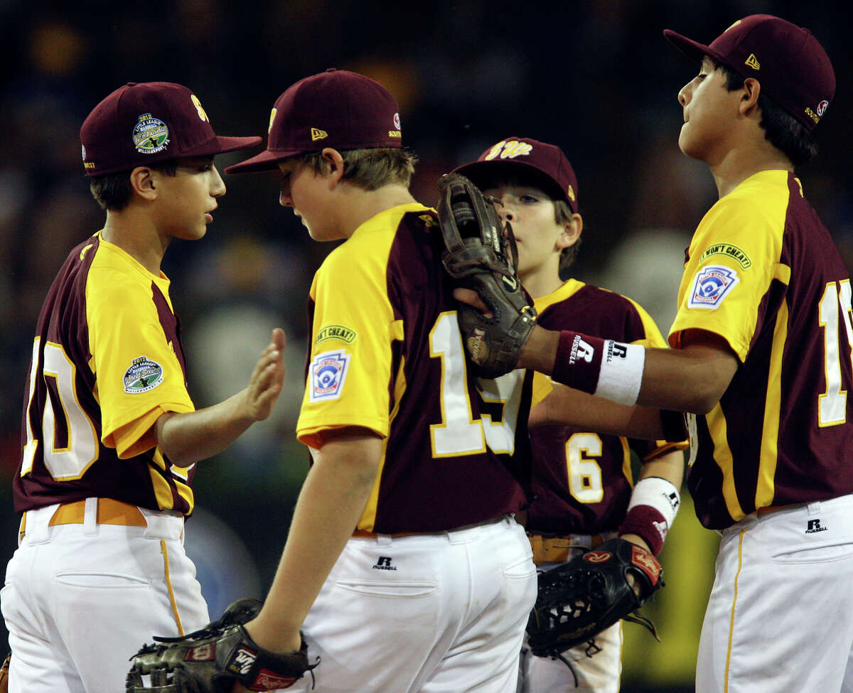San Antonio McAllister Park pitcher Carter Elliott, center, gets encouragement from teammates, from left, Grant Gomez, Samuel Serchay and Zachary Sanchez in an elimination game against Petaluma, California at the 2012 Little League World Series in South Williamsport, Pennsylvania, Thursday, Aug. 23, 2012. San Antonio lost 11-1.