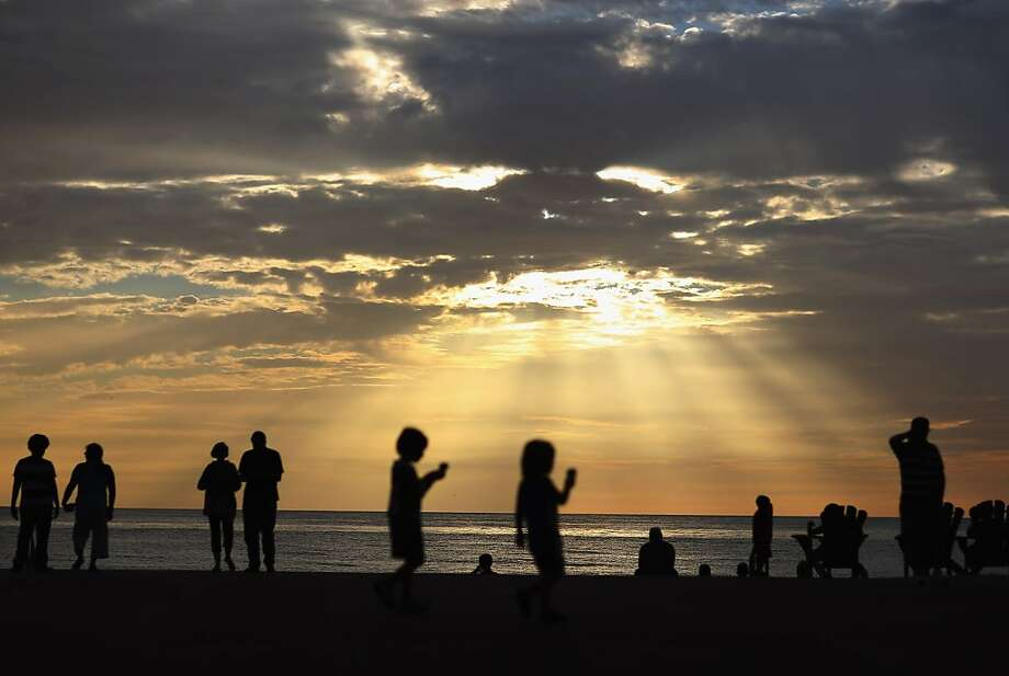 The sun sets as people enjoy the view as the region prepares for the possible arrival of Tropical Storm Isaac, which could reach hurricane strength and disrupt the Repulican National Convention, on August 23, 2012 in St Pete Beach, Florida. The storm may reach the area as the Repulican National Convention being held in Tampa, Florida begins on Monday. Photo: Joe Raedle, Getty Images