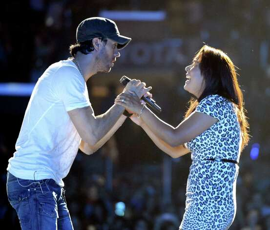 LOS ANGELES, CA - AUGUST 16:  Singer Enrique Iglesias and an audience member perform at The Staples Center on August 16, 2012 in Los Angeles, California. Photo: Kevin Winter, Getty Images / 2012 Getty Images
