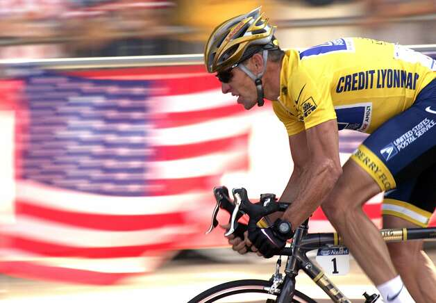 FILE - In this July 25, 2004 file photo, overall leader Lance Armstrong, of Austin, Texas, rides down the Champs Elysees avenue past U.S. flags during the 20th and last stage of the Tour de France cycling race between Montereau, southeast of Paris, and the Champs-Elysees in Paris. Federal prosecutors said, Friday, Feb. 3, 2012, they are closing a criminal investigation of Armstrong and will not charge him over allegations the seven-time Tour de France winner used performance-enhancing drugs. (AP Photo/Franck Prevel, File) (AP)