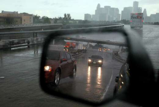 Rain brought a wet commute into downtown Houston  on Friday, Aug. 24. Photo: Mayra Beltran, Houston Chronicle / © 2012 Houston Chronicle