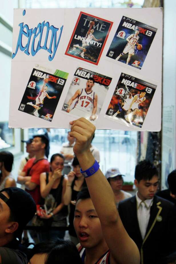 A fan holds a board pasted with cover pages of magazines with photos of NBA star Jeremy Lin during a fan meeting in Hong Kong Friday, Aug. 24, 2012. Lin will move to Yao Ming's former team Houston Rockets next season on a three-year deal. (AP Photo/Kin Cheung) Photo: Kin Cheung, Associated Press / AP