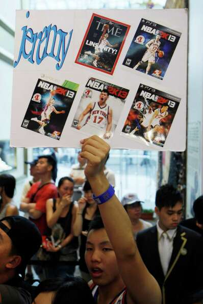 A fan holds a board pasted with cover pages of magazines with photos of NBA star Jeremy Lin during a
