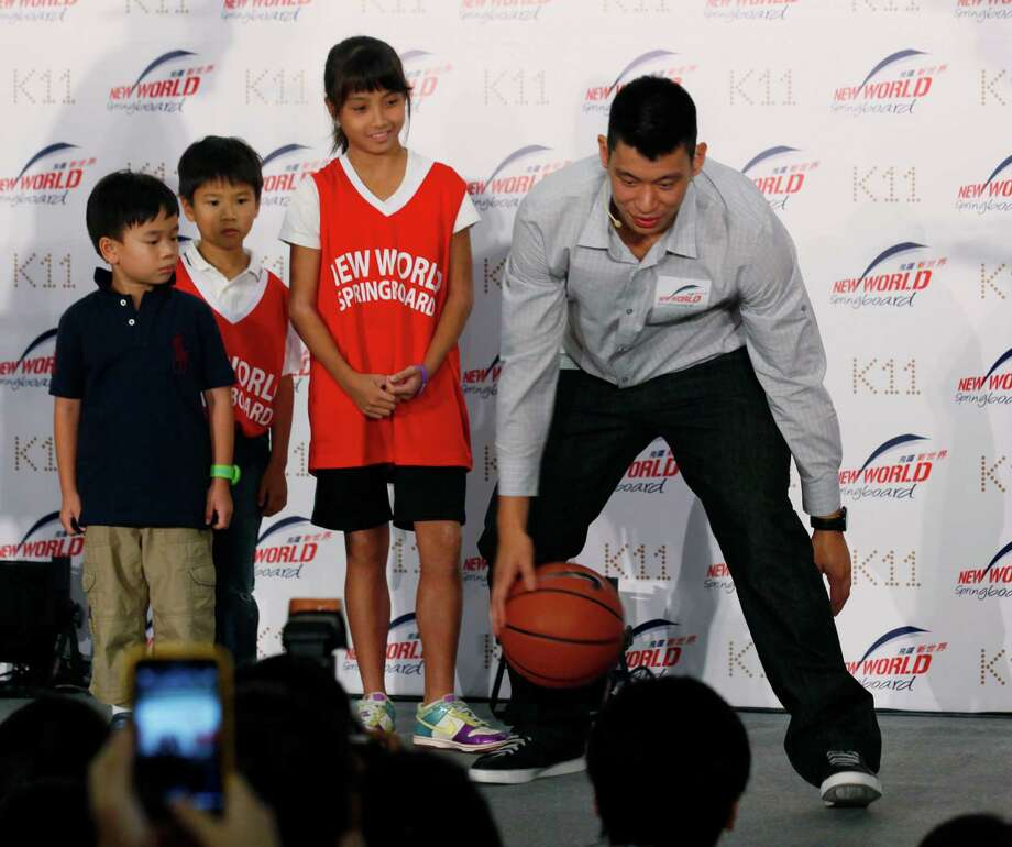 NBA basketball player Jeremy Lin, right, demonstrates his skill during a fan meeting in Hong Kong Friday, Aug. 24, 2012.  Lin will play for Houston Rockets, a team China's former NBA player Yao Ming used to be with, next season on a three-year contract. (AP Photo/Kin Cheung) Photo: Kin Cheung, Associated Press / AP
