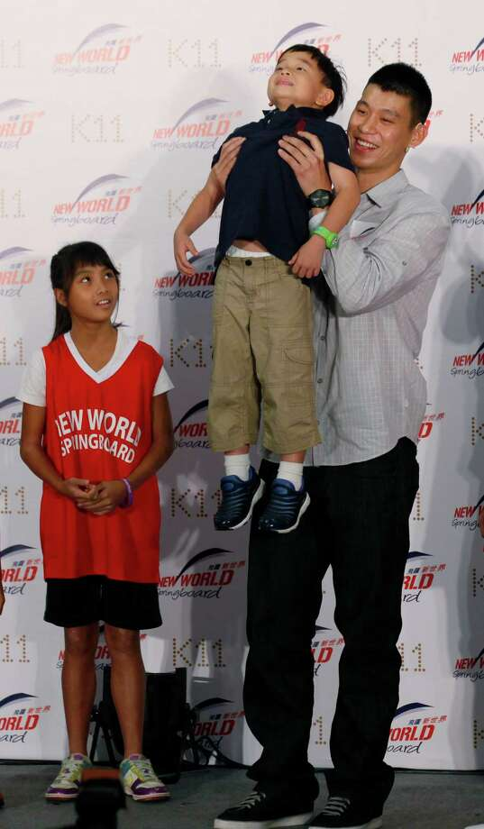 NBA basketball player Jeremy Lin holds a child during a fan meeting in Hong Kong Friday, Aug. 24, 2012. Lin will play for Houston Rockets, a team China's former NBA player Yao Ming used to be with, next season on a three-year contract. (AP Photo/Kin Cheung) Photo: Kin Cheung, Associated Press / AP
