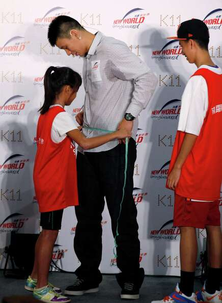 A child measures the waist of NBA basketball player Jeremy Lin during a fan meeting in Hong Kong Fri