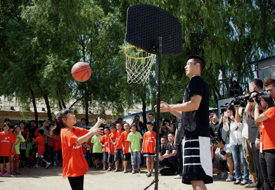 The Houston Rockets Jeremy Lin, right, watches a child playing a basketball during a basketball clinic at a school in Changping, on the outskirts of Beijing, Thursday, Aug. 9, 2012. (AP Photo/Andy Wong) Photo: Andy Wong, Associated Press / AP