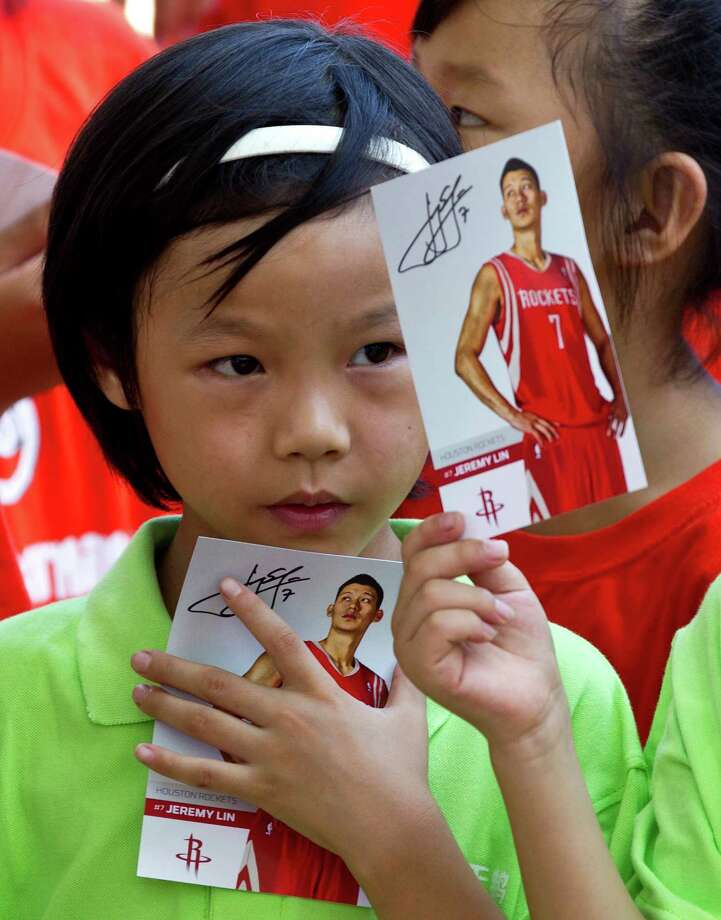 School children hold picture cards of NBA player, the Houston Rockets, Jeremy Lin after his basketball clinic at a school in Changping, on the outskirts of Beijing, Thursday, Aug. 9, 2012. (AP Photo/Andy Wong) Photo: Andy Wong, Associated Press / AP