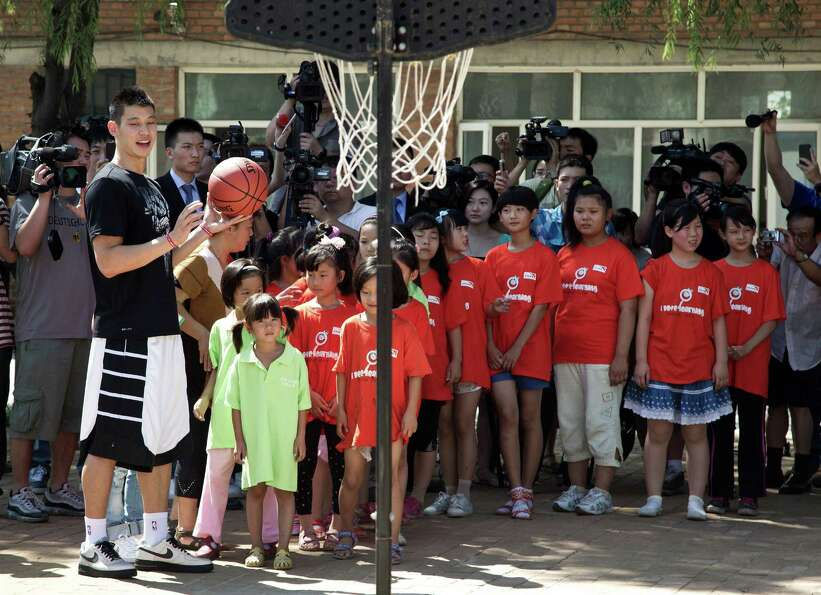 NBA Houston Rockets' player Jeremy Lin, left, teaches children during a basketball clinic at a schoo