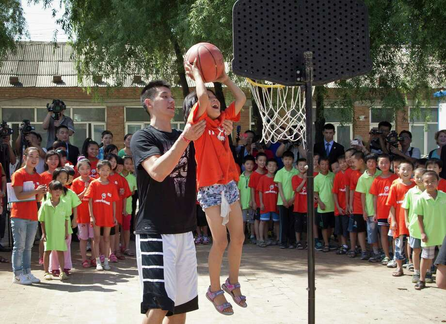 The Houston Rockets Jeremy Lin helps a child to slum a dunk during a basketball clinic at a school in Changping, on the outskirts of Beijing, Thursday, Aug. 9, 2012. (AP Photo/Andy Wong) Photo: Andy Wong, Associated Press / AP