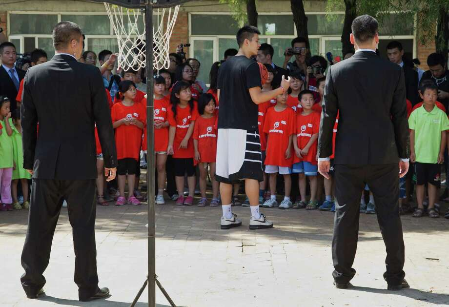 Bodyguards watch NBA Houston Rockets' player Jeremy Lin, center, chatting with children during his basketball clinic at a school in Changping, on the outskirts of Beijing, Thursday, Aug. 9, 2012. (AP Photo/Andy Wong) Photo: Andy Wong, Associated Press / AP