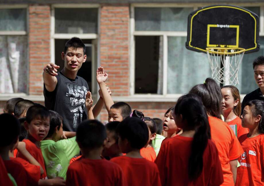 NBA Houston Rockets' player Jeremy Lin teaches children during a basketball clinic at a school in Changping, on the outskirts of Beijing, Thursday, Aug. 9, 2012. (AP Photo/Andy Wong) Photo: Andy Wong, Associated Press / AP