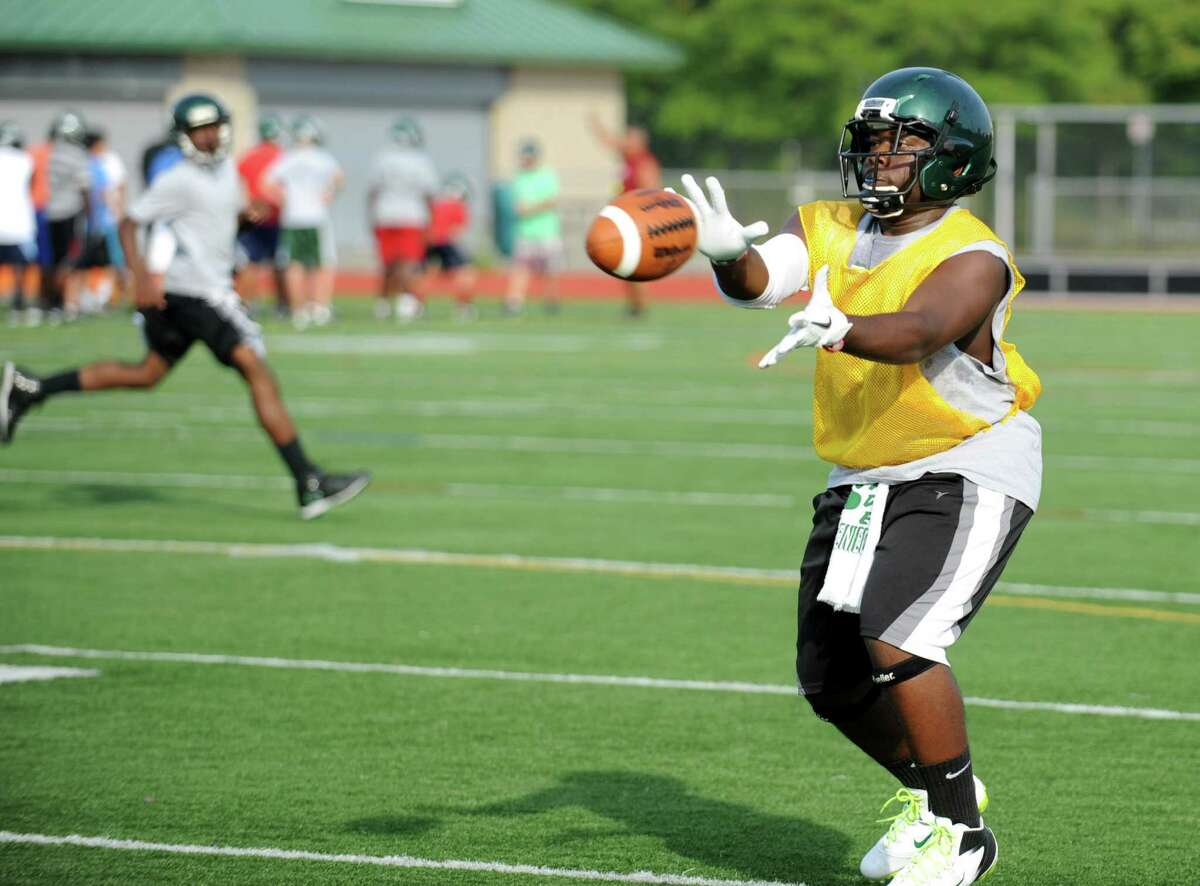 Senior Tomar Joseph reaches for a pass during Norwalk High School's football practice at the school on Friday August 24, 2012.