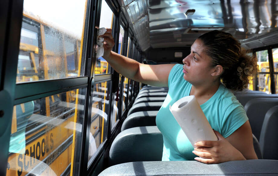 Jessica Rivera, 30, of Bethel, a first-year school bus driver for Student Transportation of America Inc., cleans the windows on her school bus Friday, Aug. 24, 2012. Photo: Carol Kaliff