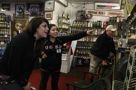 Melissa Robles (left) from Fresno sees a picture of herself nine years ago at Piccolo Pete in San Francisco, Calif., while visiting her best friend Bessy Moreno (middle) on Thursday, August 23, 2012. Bessy  is the daughter of owner John C. Siri (right), who has pictures of family and customers pinned behind the counter.