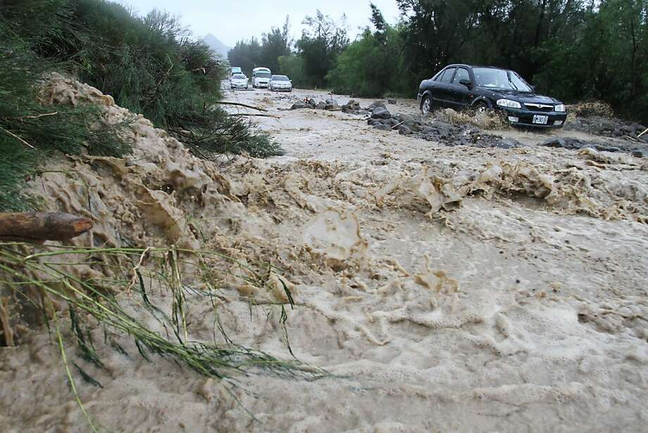 Cars make their way through a road affected by a mud slide caused by heavy rain dumped by Typhoon Tembin in Pingtung County, Southern Taiwan, on August 24, 2012. Tembin Typhoon Tembin swept across southern Taiwan, toppling trees and ripping off rooftops after thousands of people were evacuated to avoid a repeat of a deadly storm three years ago.  Photo: Afp, AFP/Getty Images