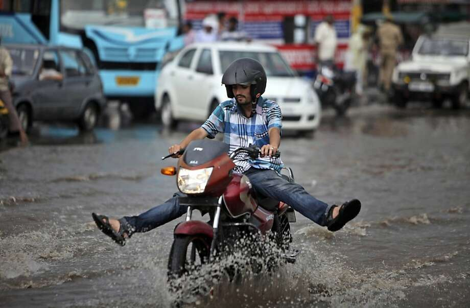 An Indian man holds his legs up to prevent them from getting wet as he rides a motorbike through a waterlogged road after monsoon showers in Jammu, India, Friday, Aug. 24, 2012. The monsoon rains which usually hit India from June to September are crucial for farmers whose crops feed hundreds of millions of people.  Photo: Channi Anand, Associated Press