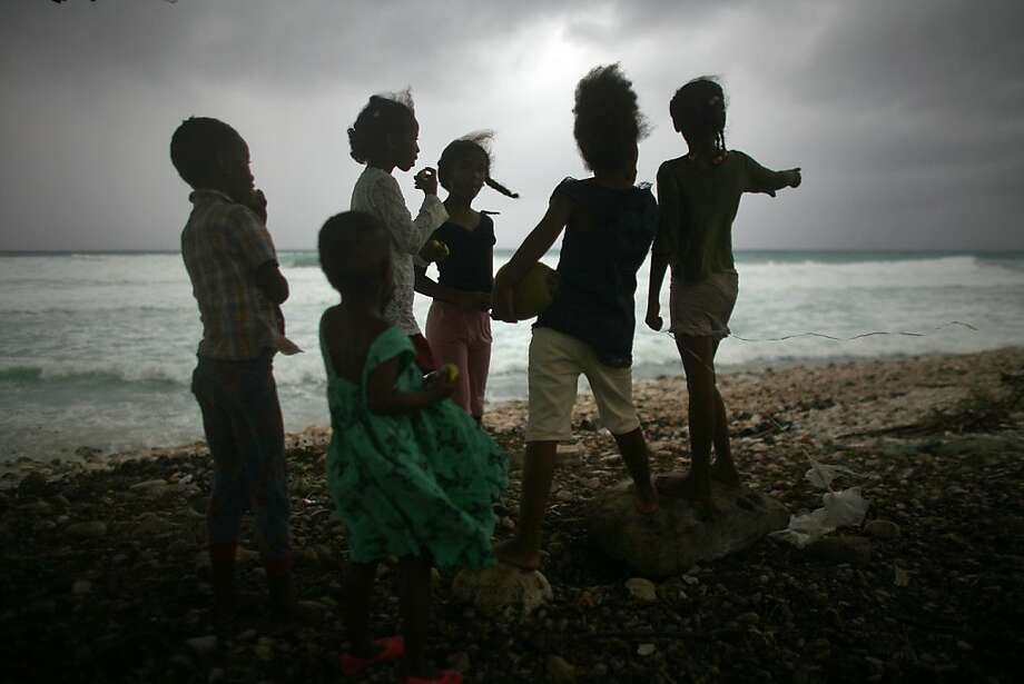 Children look out at the beach as Tropical Storm Isaac approaches in Barahona, Dominican Republic, Friday, Aug. 24, 2012.  Isaac strengthened slightly as it spun toward the Dominican Republic and Haiti, but seemed unlikely to gain enough steam early Friday to strike the island of Hispaniola as a hurricane. The storm's failure to gain the kind of strength in the Caribbean that forecasters initially projected made it more likely that Isaac won't become a hurricane until it enters the Gulf of Mexico, said Eric Blake, a forecaster with U.S. National Hurricane Center in Miami. Photo: Ricardo Arduengo, Associated Press
