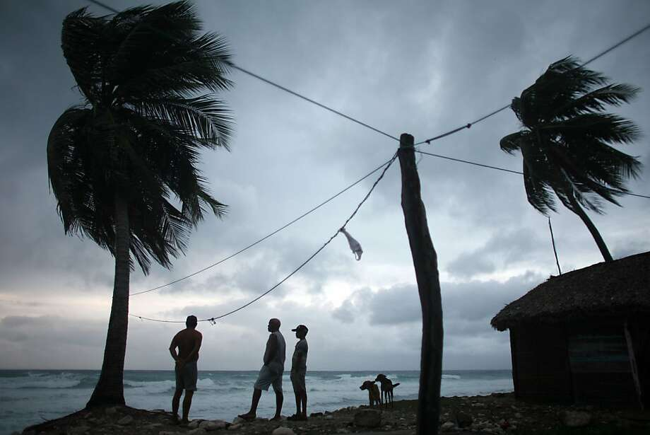 People look out at the beach as Tropical Storm Isaac approaches in Barahona, Dominican Republic, Friday, Aug. 24, 2012.   Isaac strengthened slightly as it spun toward the Dominican Republic and Haiti, but seemed unlikely to gain enough steam early Friday to strike the island of Hispaniola as a hurricane. The storm's failure to gain the kind of strength in the Caribbean that forecasters initially projected made it more likely that Isaac won't become a hurricane until it enters the Gulf of Mexico, said Eric Blake, a forecaster with U.S. National Hurricane Center in Miami.  Photo: Ricardo Arduengo, Associated Press