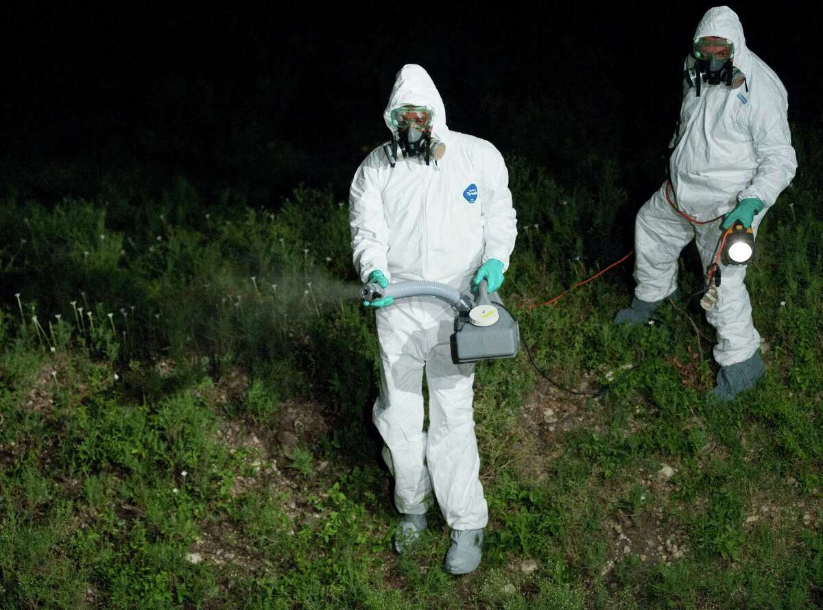 502nd Civil Engineering Squadron employees Keith Foster, left, and Al Salazar, spray insecticide fog to kill mosquitoes potentially infected with the West Nile virus, Friday, Aug. 24, 2012, at Fort Sam Houston in San Antonio.
