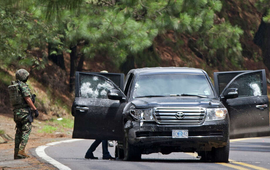 An armored U.S. Embassy vehicle is checked by military personal after it was attacked by unknown assailants on the highway leading to the city of Cuernavaca, near Tres Marias, Mexico, Friday, Aug. 24, 2012. Two U.S.  government employees were shot and wounded in an attack on their vehicle south of Mexico City on Friday, a law enforcement official said. Photo: Alexandre Meneghini, Associated Press / AP