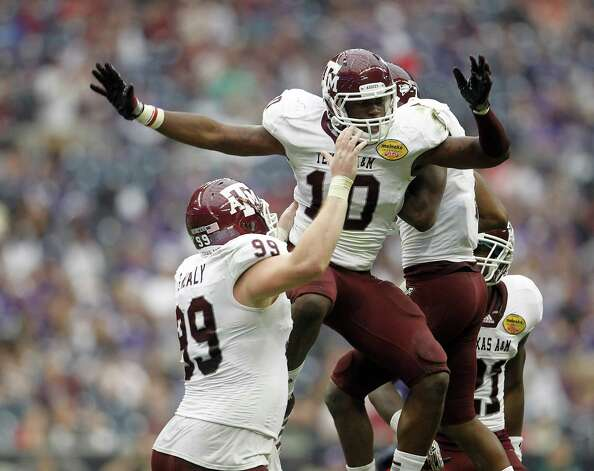 Texas A&M Aggies linebacker Sean Porter (10) celebrates his sack on a third down of Northwestern Wildcats quarterback Dan Persa (7) forcing the punt during the third quarter of the Meineke Car Care Bowl at Reliant Stadium,Saturday, Dec. 31, 2011, in Houston.  Texas A&M won the game against Northwestern University 33-22. Photo: Karen Warren, Houston Chronicle / © 2011 Houston Chronicle