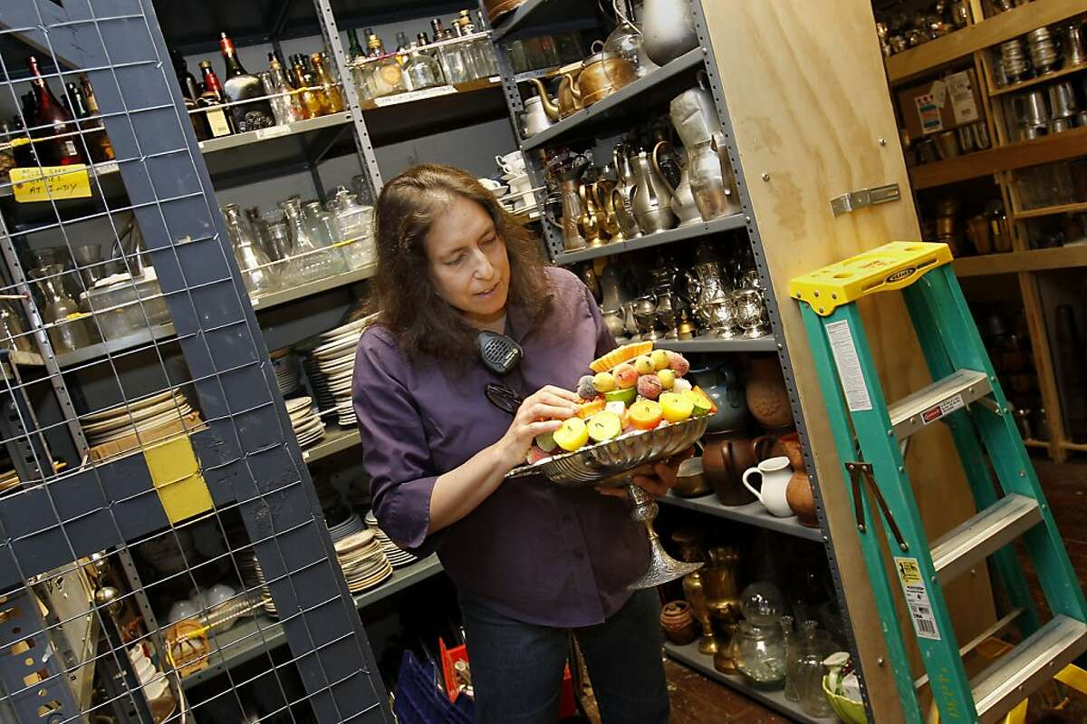 Lori Harrison examines a small treasure, a platter of fruit candles in a back room. Lori Harrison is the first female properties master at the San Francisco Opera. Props are stored throughout the catwalks, on shelves, in every nook and cranny at Opera House.