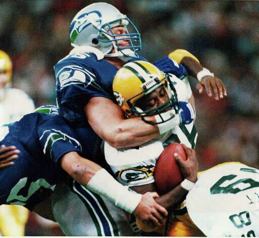 Seattle Seahawk Brian Bosworth makes a tackle in 1987 during his brief time in the NFL. The All-American had signed what was then the biggest rookie contract in NFL history, and then retired a few years later after getting injured. He went on to become a movie actor. Photo: Barry R. Sweet, ©2012 The Associated Press, published with permission. Photo: BRS / BRS