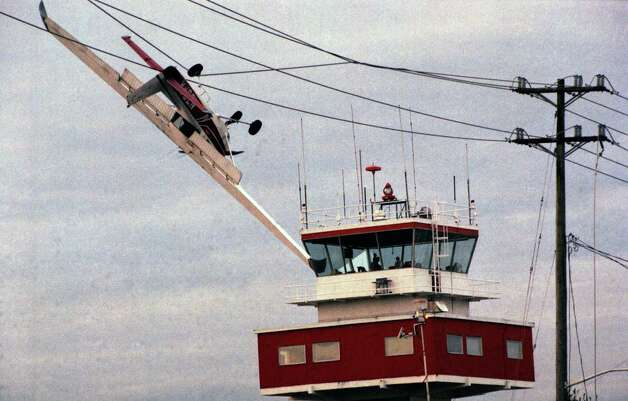A pilot crashes his single-engine Cessna into a high-voltage transmission line over Boeing Field on April 9, 1998, causing it to hang upside down for hours while firefighters extricated him. He survived. Photo: Barry R. Sweet, ©2012 The Associated Press, published with permission. Photo: BARRY SWEET PHOTO / BARRY SWEET PHOTO