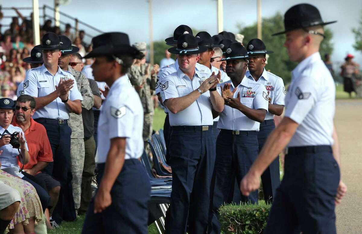 Military Training Instructors applaud new MTI's as they march by after reciting the MTI Pledge at the Air Force Basic Military Training graduation parade at Lackland Air Force Base. Friday, August 24, 2012.