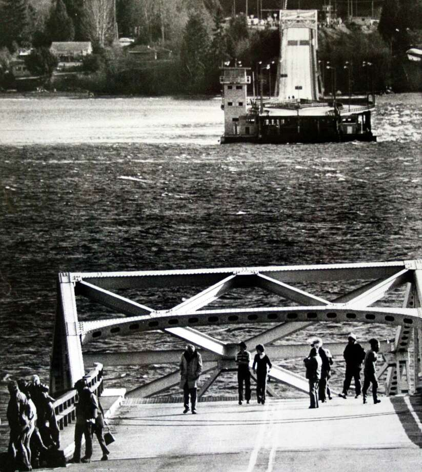 People stand on what's left of the Hood Canal floating bridge after it sinks on Feb. 14, 1979, less than 20 years after it was built to connect the Olympic and Kitsap peninsulas. The bridge had failed during a powerful windstorm. Photo: Barry R. Sweet, @2012 The Associated Press, published with permission. Photo: X