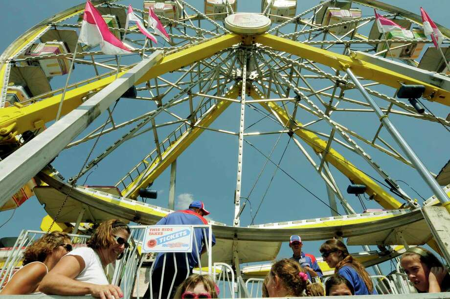 Riders wait to ride the giant Ferris wheel during the Columbia County Fair in Chatham Thursday afternoon. 9/02/2010. The fair is open daily 10am-11p.m thru 9/6/2010 ( Michael P. Farrell / Times Union ) Photo: Michael P. Farrell / 00010019A