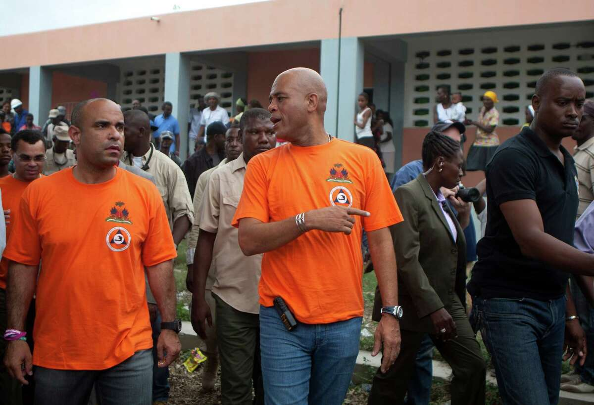 Haiti's President Michel Martelly, center, and Prime Minister Laurent Lamothe, left, visit people who were displaced by the 2010 earthquake and who live in a tent shelter, where they will wait out Tropical Storm Isaac in Port-au-Prince, Haiti, Friday, Aug. 24, 2012. Tropical Storm Isaac strengthened slightly as it spun toward the Dominican Republic and vulnerable Haiti on Friday, threatening to bring punishing rains but unlikely to gain enough steam to strike as a hurricane. (AP Photo/Dieu Nalio Chery)
