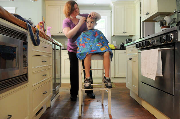 Geraldine McKeon, owner of Haircuts at Home, cuts Jack Tracey's hair at his family's home in Norwalk, Conn., August 17, 2012.  McKeon owns a salon in Milford but also offers a service that travels all over Fairfield County to provide salon services to elderly and homebound residents. Photo: Keelin Daly / Stamford Advocate