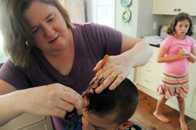 Geraldine McKeon, owner of Haircuts at Home, cuts Jack Tracey's hair as his sister, Maddie, 10, looks on at their family's home in Norwalk, Conn., August 17, 2012.  McKeon owns a salon in Milford but also offers a service that travels all over Fairfield County to provide salon services to elderly and homebound residents. Photo: Keelin Daly / Stamford Advocate