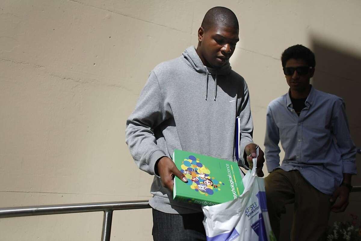 SFSU freshman Chukwuemeka Elendu (left) puts a new textbook in his bag as he talks with his roommate, Vikram Valluria.