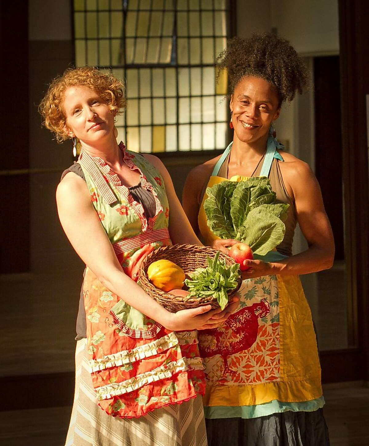 Amara Tabor-Smith, (African American) and Lisa Wymore hold a basket of vegetables at the UC Bancroft Dance Studio in Berkeley, Calif., on Friday, August 24th, 2012. They are holding a dance work shop called