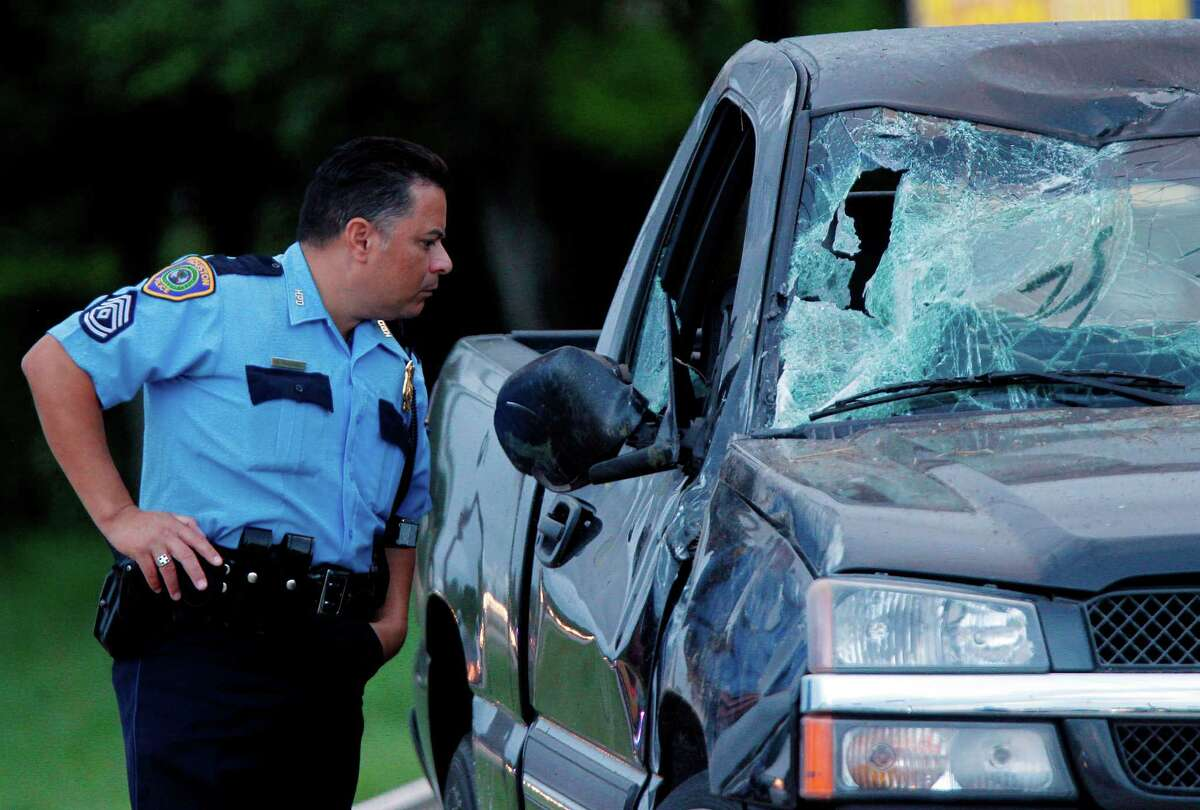 A Houston police officer gets a look inside of the pick up truck where a man was ejected and died from his injuries after the truck rolled several times in southwest Houston early Friday morning on Friday, Aug. 24, 2012, in Houston. The crash happened about 5:45 a.m. in the 11900 block of Almeda near W. Airport, according to the Houston Police Department, the driver bumped the curb while traveling north on Alameda Road, and rolled the truck attempting to correct his mistake.