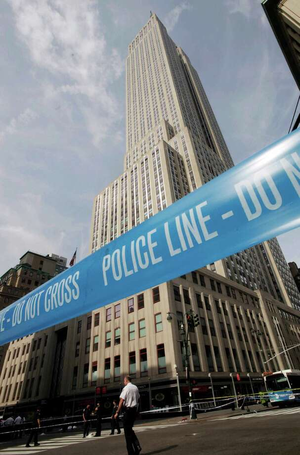 Police crime scene tape blocks 34th St. at Fifth Avenue after a multiple shooting outside the Empire State Building, Friday, Aug. 24, 2012, in New York.  At least four people were shot on Friday morning and the gunman was dead, New York City officials said. A witness said the gunman was firing indiscriminately. Police said as many as 10 people were injured, but it is unclear how many were hit by bullets. A law enforcement official said the shooting was related to a workplace dispute. The official spoke on condition of anonymity because the investigation was ongoing. (AP Photo/Mark Lennihan) Photo: Mark Lennihan