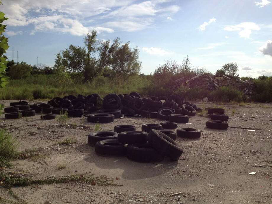 A far southwest former Houston auto parts lot is cleared of vehicles but remains piled high with tires, which are possible locations for mosquito breeding. Photo: Cindy George / Houston Chronicle