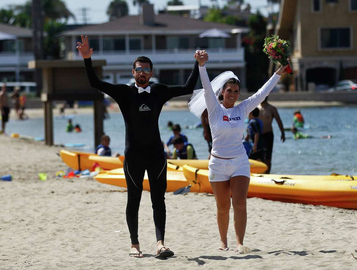 Grant Engler and his fiance, Amanda Vulf, arrive for their jet pack wedding wearing various forms of wet suit gear, Thursday, Aug. 23, 2012 in Newport Beach, Calif. The 25-year-old former wedding planner from Grand Rapids, Mich., says she wanted a unique ceremony. So the couple donned the (Canadian) $90,000 (C72,000) contraptions on their backs, along with a wetsuit for the groom and white board shorts and a rash-guard shirt for the bride. The jet packs from Jetlev Southwest helped the couple hover a few feet above the water, to the cheers of their wedding guests. Everything went smoothly, except for a kayaker who capsized during the newlyweds' first dance on the water. (AP Photo/Lenny Ignelzi)