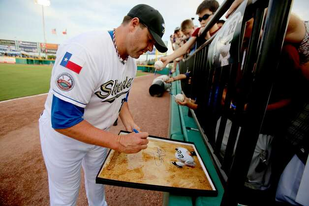Roger Clemens signs autographs before his first game in Skeeters uniform. (Thomas B. Shea / For the Chronicle)