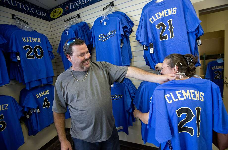 Charles Collins checks out the sizing of a Roger Clemens Skeeters shirt. (Thomas B. Shea / For the Chronicle)