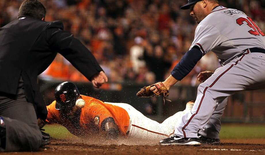 San Francisco Giants Pablo Sandoval slides safley into home plate scoring on a passed ball by Atlanta Braves pitcher Ben Sheets right after he dropped the throw from Braves catcher Brian McCann during the third inning of their MLB baseball game Friday, August 24, 2012 in San Francisco Calif. Photo: Lance Iversen, The Chronicle