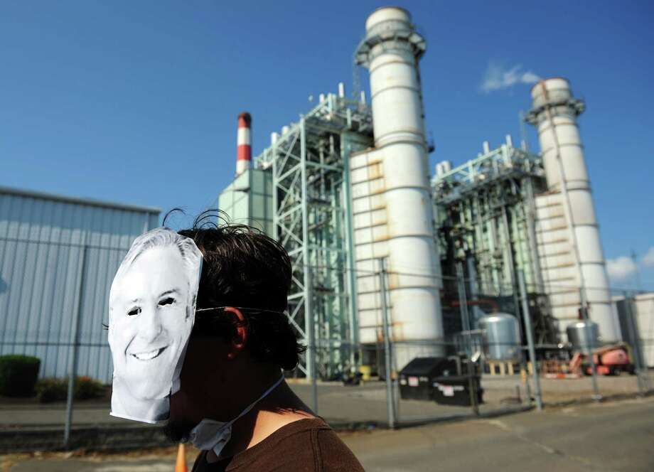 Jayson Castillo, 23, of Great Neck, NY, wears a Bill Finch mask during a rally in front of the gate of the PSEG coal plant on Atlantic Street in Bridgeport Saturday, August 4, 2012.  Castillo and other activists marched from City Lights Art Gallery to the Bridgeport Harbor Power Station where they demonstrated against the use of fossil fuels and in favor of clean energy and green jobs. Photo: Autumn Driscoll / Connecticut Post