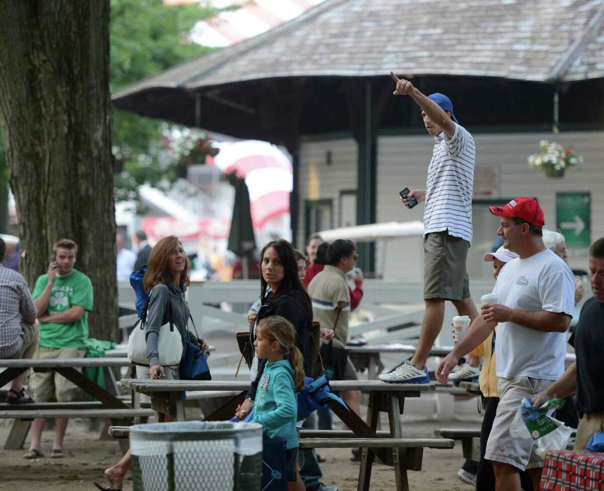Chris Calogero uses his cell phone and waves to get the attention of his friends who are joining him after securing his spot in the picnic area at the Saratoga Race Course in Saratoga Springs, N.Y. Travers Day Aug. 25, 2012. (Skip Dickstein/Times Union)